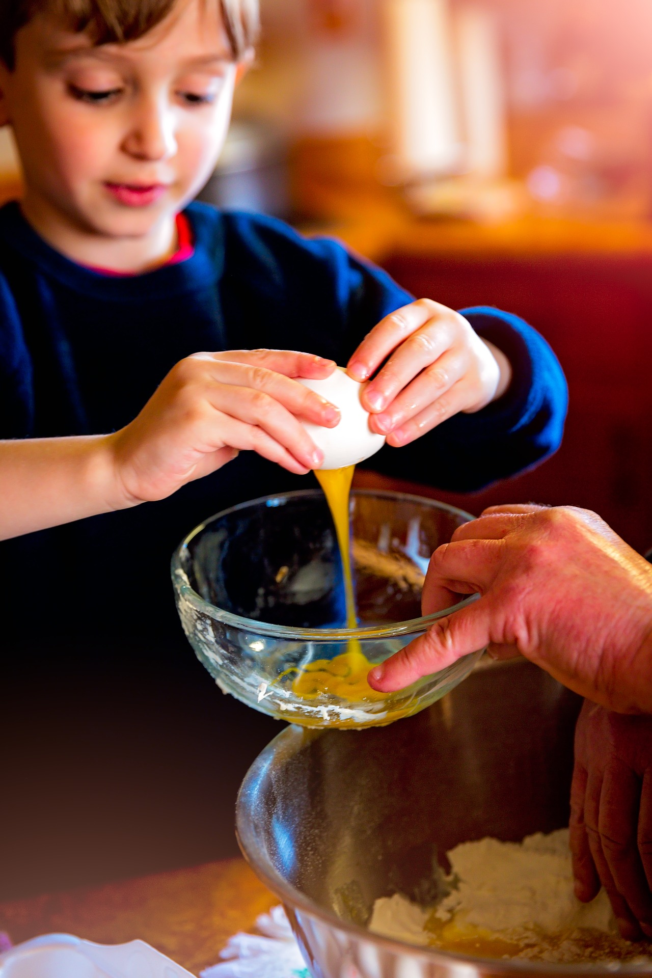 a boy holds on to both ends of an egg with his hands while the egg yolk oozes out of the middle of the egg an into a bowl